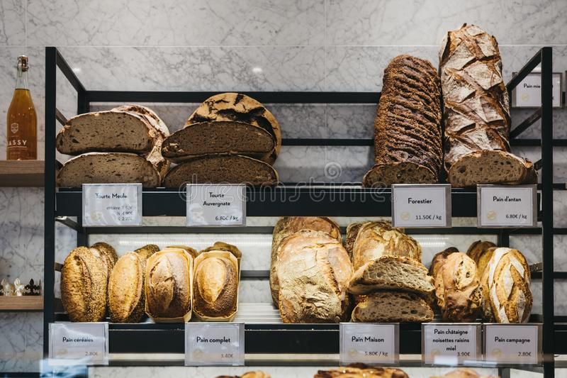 Variation av nytt hantverkarebröd på försäljning på en bageriboulangerie i Paris, Frankrike fotografering för bildbyråer
