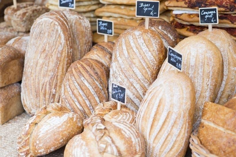 Variation av organiskt nytt bakat bröd på artisanal bageriskärm arkivfoto