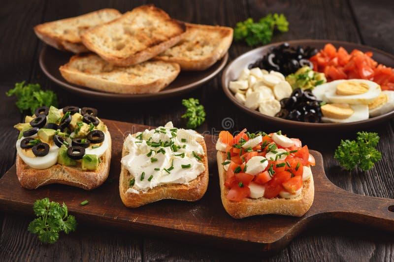 Variation av smörgåsar med tomater, mozzarellaen, avokadot, ägg och gräddost royaltyfri bild