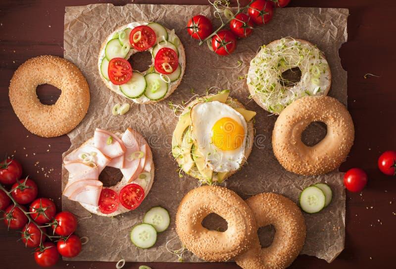 Variation av smörgåsar på baglar: ägg avokado, skinka, tomat som är mjuk royaltyfri fotografi