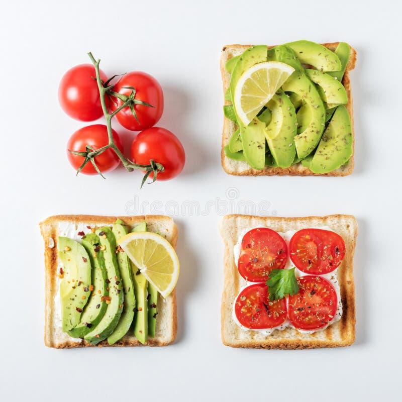 Variation av sunda frukostrostade bröd med avokadot och körsbärsröda tomater på vit bakgrund arkivbilder