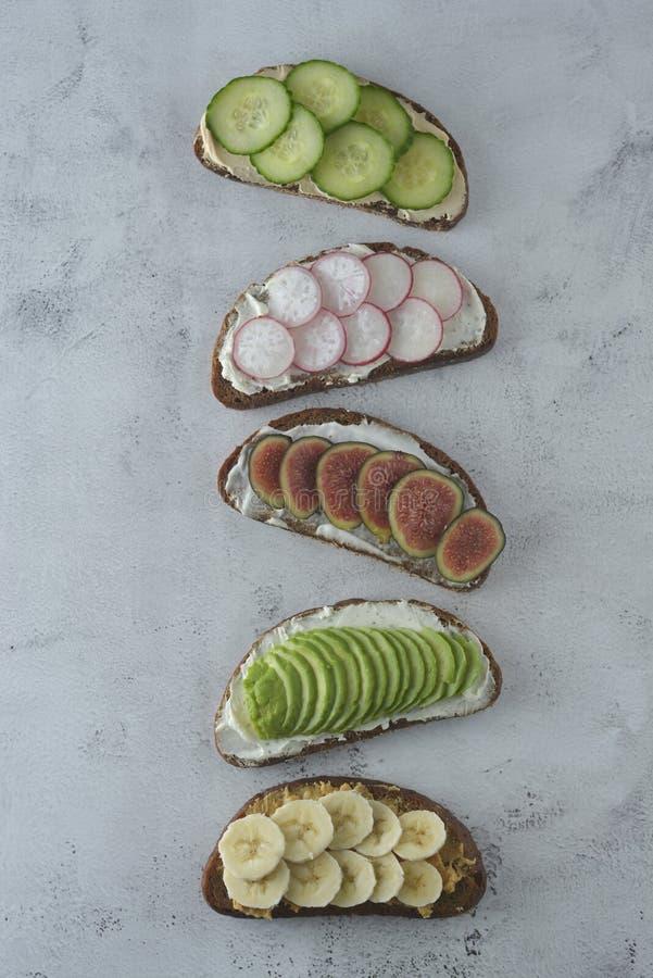 Variation av sunda frukostsmörgåsar med avokadot, gurkan, fikonträdfrukt, bananen, gräddost och wholegrain bröd royaltyfria bilder