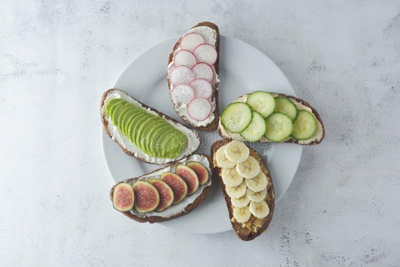 Variation av sunda frukostsmörgåsar med avokadot, gurkan, fikonträdfrukt, bananen, gräddost och wholegrain bröd royaltyfria foton