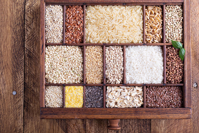 Variation av sunda korn och frö i en träask arkivfoto