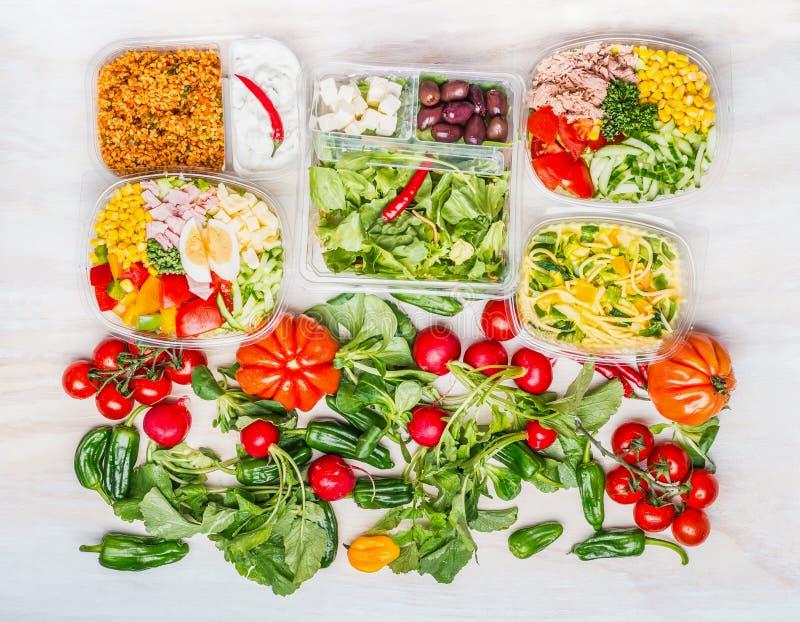 Variation av sunda sallader i lunchaskar med vit träbakgrund för ingredienser arkivbilder