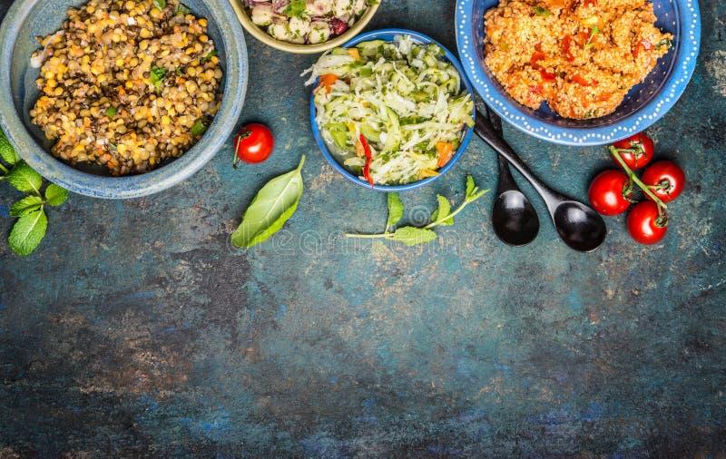 Variation av sunda vegetariska sallader i lantliga bunkar med skedar på tappningbakgrund, bästa sikt, ställe för text, gräns arkivbilder