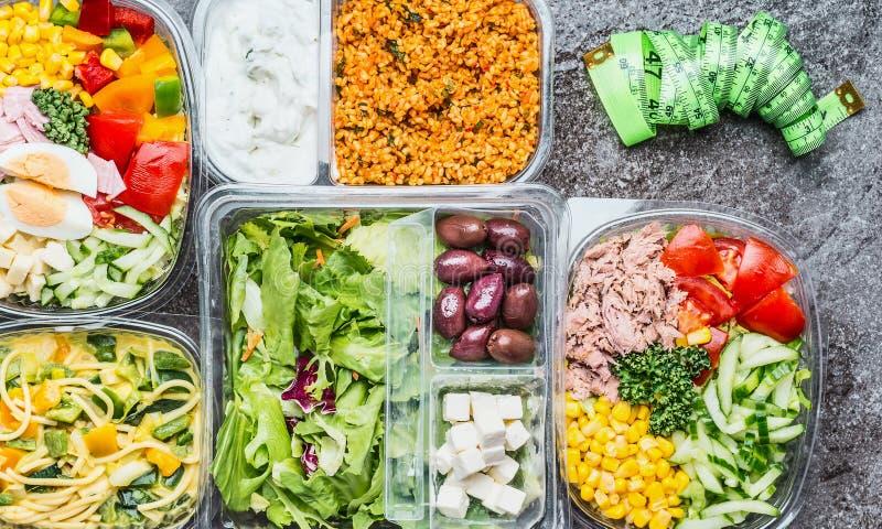 Variation av sunt bantar lunchaskar med grönsaker sallad och mätningsbandet Salladbunkar i plast- packar med mätning royaltyfri bild