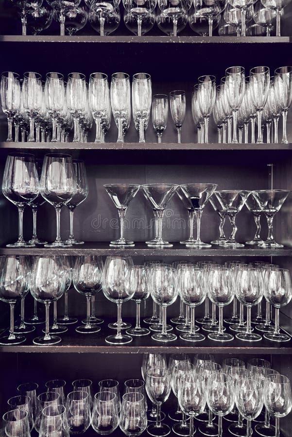 Variation av tomma crystal exponeringsglas på hyllor arkivfoton