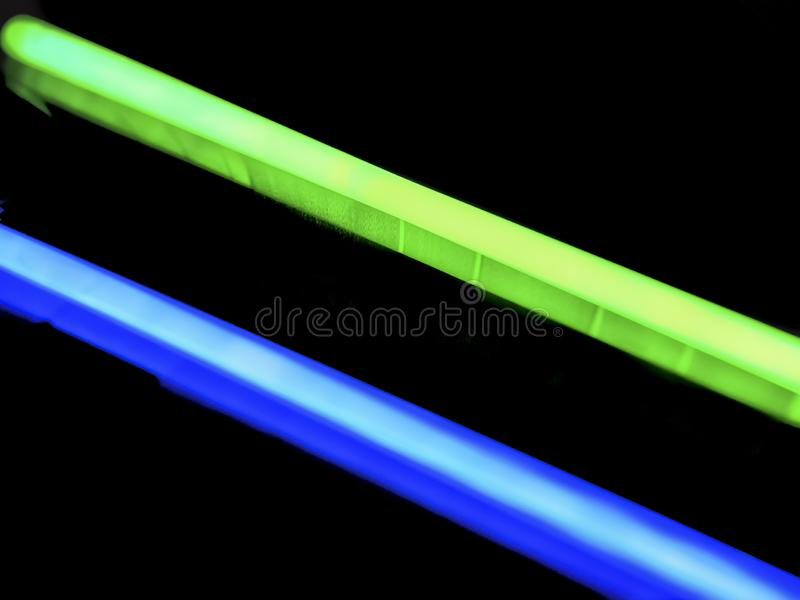 Multicolor fluorescent chem light neon black background. Variation of multicolored blue green colorful colored fluorescent chem light neon tube with reflection stock images