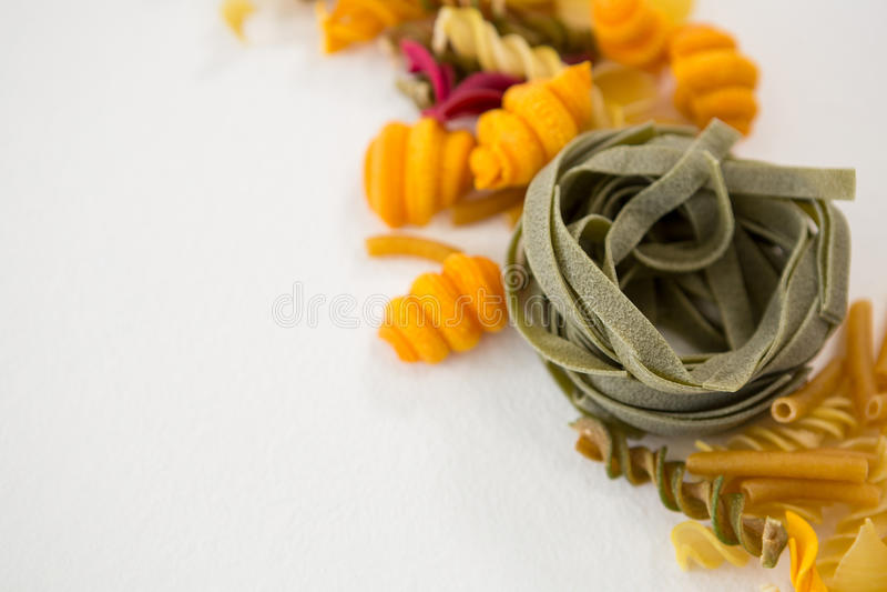 Variationer av pasta som är ordnade på vit bakgrund royaltyfri fotografi