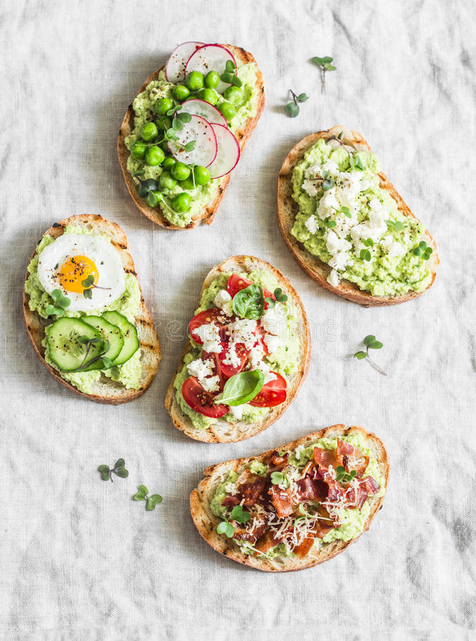 Variationsavokadosmörgås - med frasig bacon, vaktelägg, tomater, getost, gröna ärtor, rädisa, gurka sunt mellanmål På royaltyfri bild