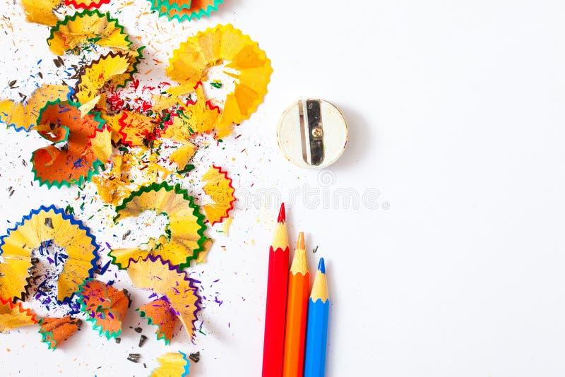 Varicolored Bleistift, Schnitzel und Bleistiftspitzer auf einem weißen lizenzfreie stockbilder