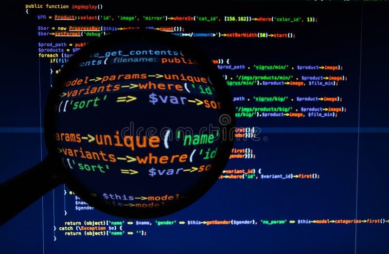 Varicoloured php code under magnifier. Front view of the varicoloured php code under magnifier stock image