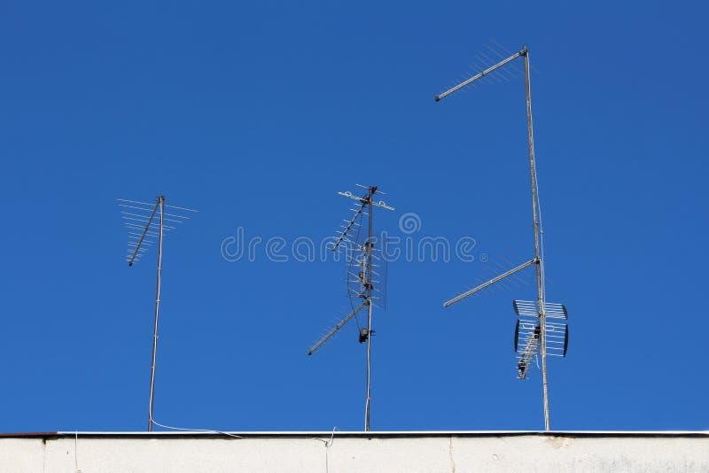 Varie antenne multiple della TV nelle forme differenti e forme montate sui pali del metallo sopra la costruzione di appartamento immagine stock libera da diritti
