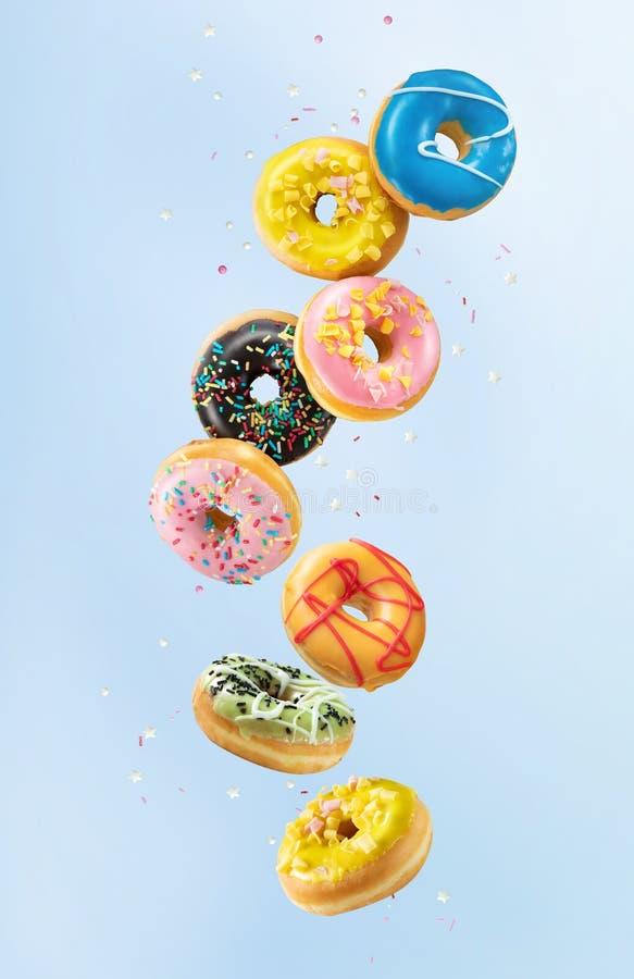 Varie ciambelle colorate in movimento su sfondo blu fotografia stock libera da diritti