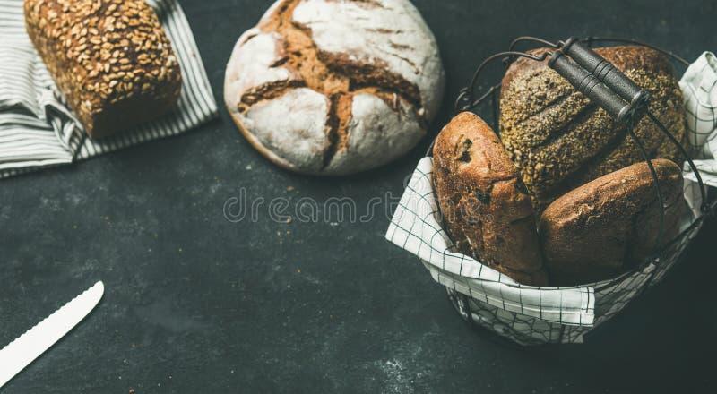 Varie pagnotte del pane sopra fondo nero, spazio della copia, composizione orizzontale fotografia stock