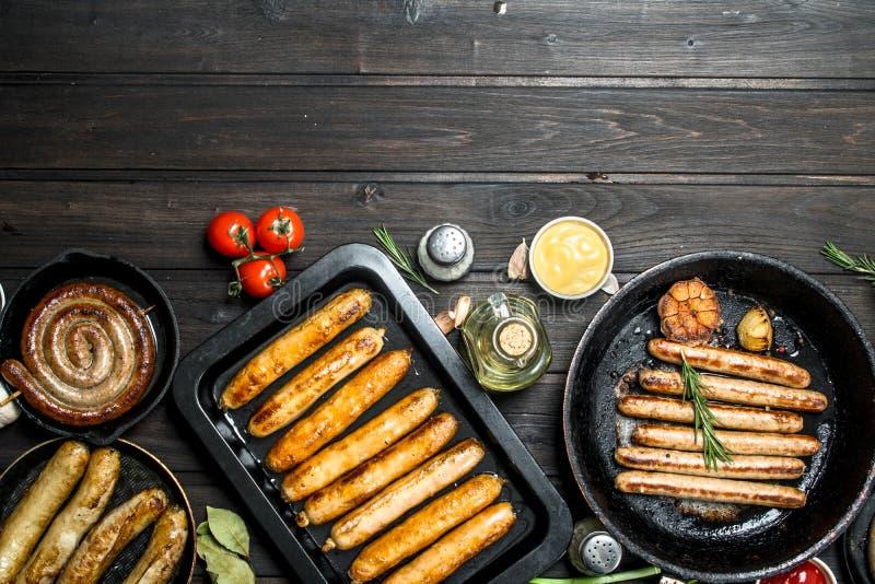 Varie salsiccie fritte con le erbe e le spezie immagini stock