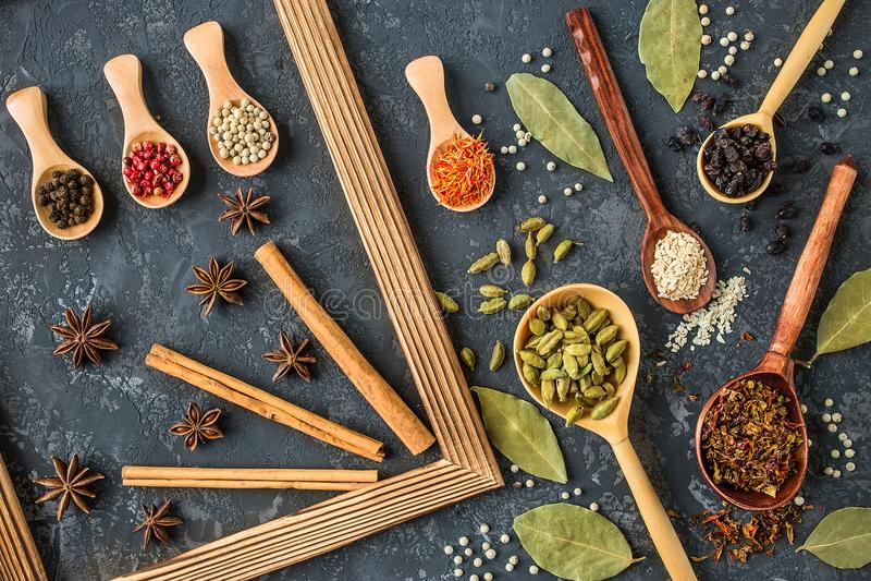 Varie spezie in cucchiai di legno sulla tavola di pietra scura fotografia stock