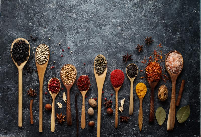 Varie spezie indiane in cucchiai, in erbe ed in dadi di legno immagine stock libera da diritti