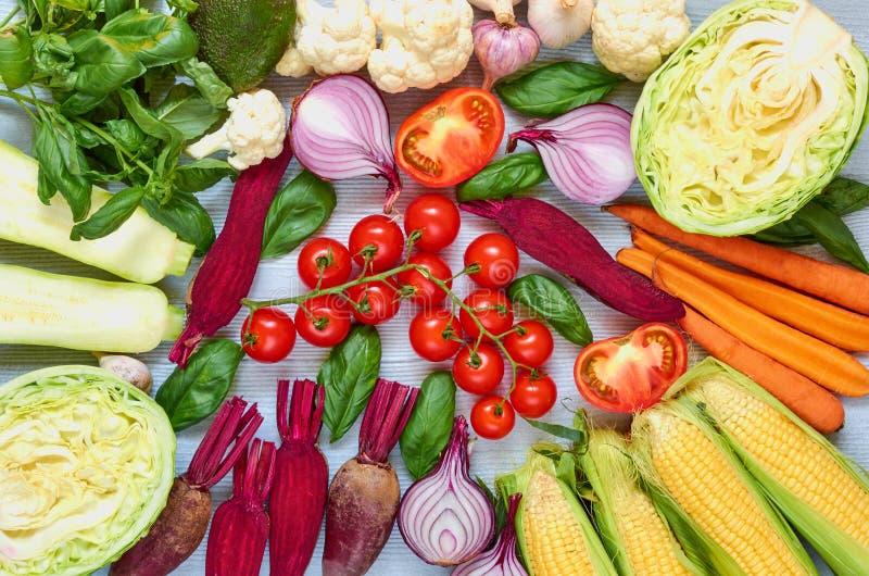 Varie verdure organiche fresche sulla tavola grigia: pomodori ciliegia, zucchini affettato, barbabietola, aglio, cavolo, carote,  fotografia stock