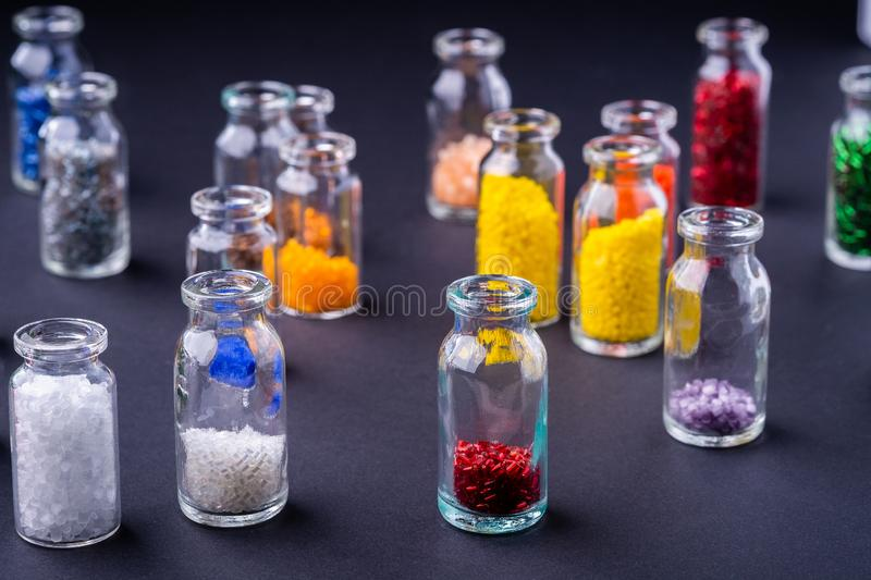 Varied colors beads in transparent bottles dark background. Macro stock photography
