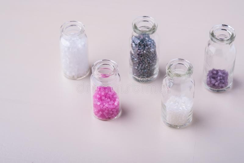 Varied colors beads in transparent bottles white background. Macro stock image