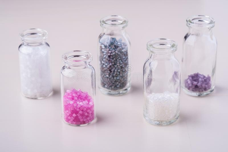 Varied colors beads in transparent bottles white background. Macro stock images