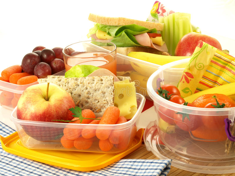 Varied lunch, isolated. Lunch with various fruits and vegetables in boxes stock photo