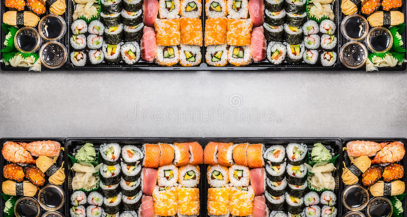 Varied Sushi sets assortment in bento boxes on gray stone background, top view stock photography