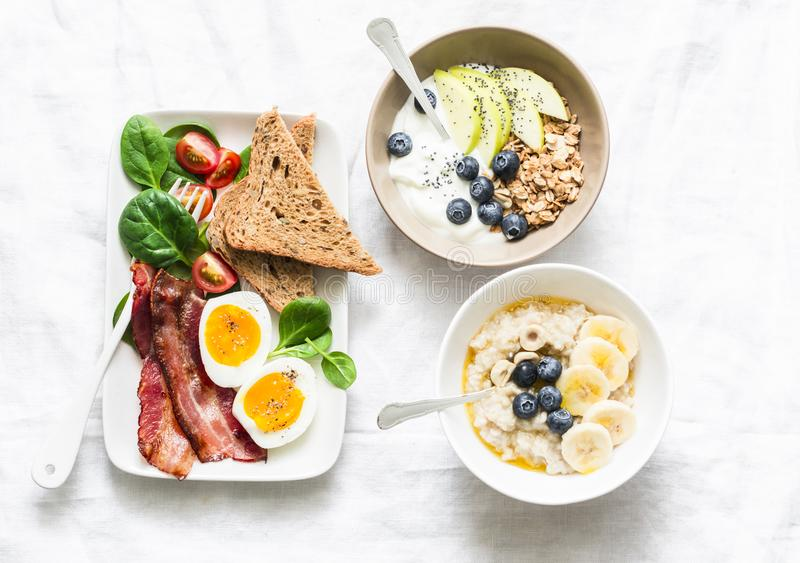 Varied sweet and savory breakfast - bacon with egg and vegetables, spinach salad, yogurt granola and fruit, vegetarian royalty free stock photo