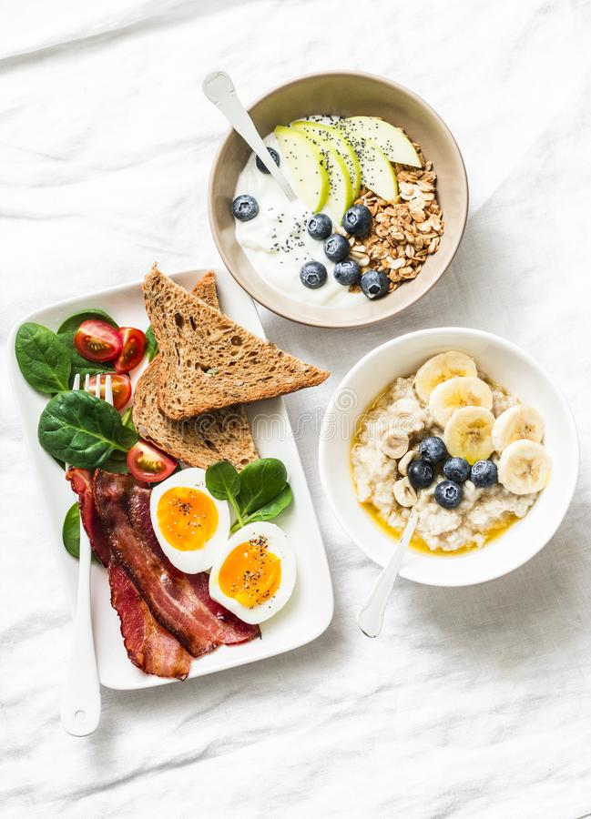 Varied sweet and savory breakfast - bacon with egg and vegetables, spinach, yogurt with granola and fruit, vegetarian stock images