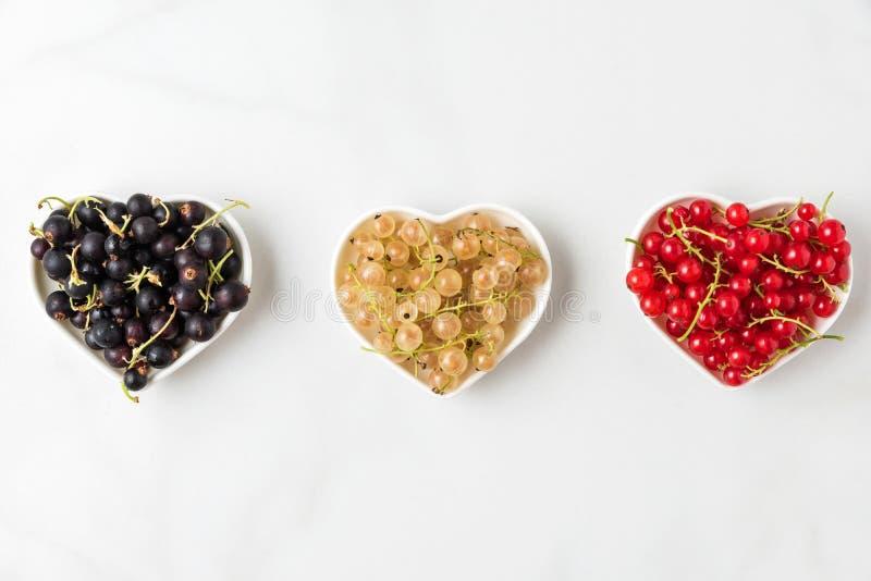 Variedad de bayas de la pasa negras, rojas y blancas en cuencos de la forma del corazón en el fondo de mármol blanco Concepto de  imagen de archivo