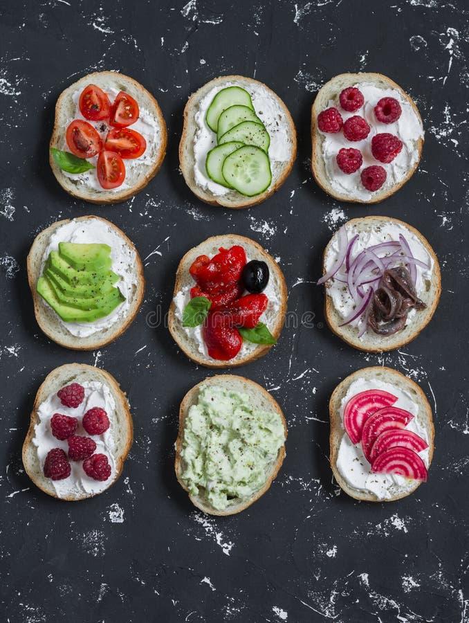 Variedad de bocadillos - los bocadillos con queso, tomates, anchoas, asaron las pimientas, frambuesas, aguacate, coronilla de la  imagen de archivo libre de regalías