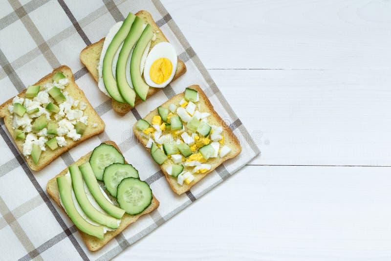 Variedad de bocadillos para el desayuno, bocado, aguacate, huevo, queso cremoso en los bocadillos del pan, fondo blanco foto de archivo