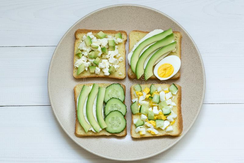 Variedad de bocadillos para el desayuno, bocado, aperitivos, aguacate, queso cremoso en los bocadillos del pan, fondo blanco fotografía de archivo