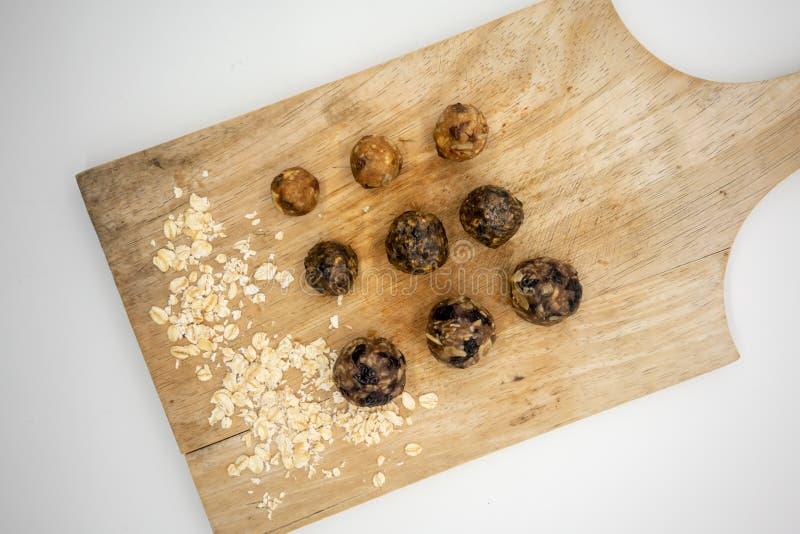 Variedad de bolas hechas en casa de la energía en filas en verraco que taja de madera fotos de archivo libres de regalías