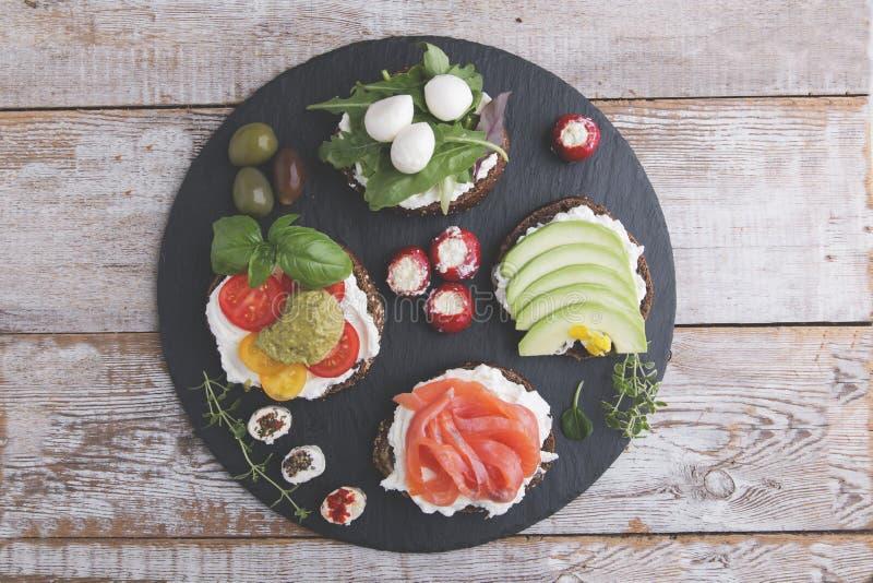 Variedad de canape con los salmones, aguacate, mozzarella, tomate, pesto, aceitunas, queso cremoso Mezcla de diversos bocados y a fotos de archivo libres de regalías
