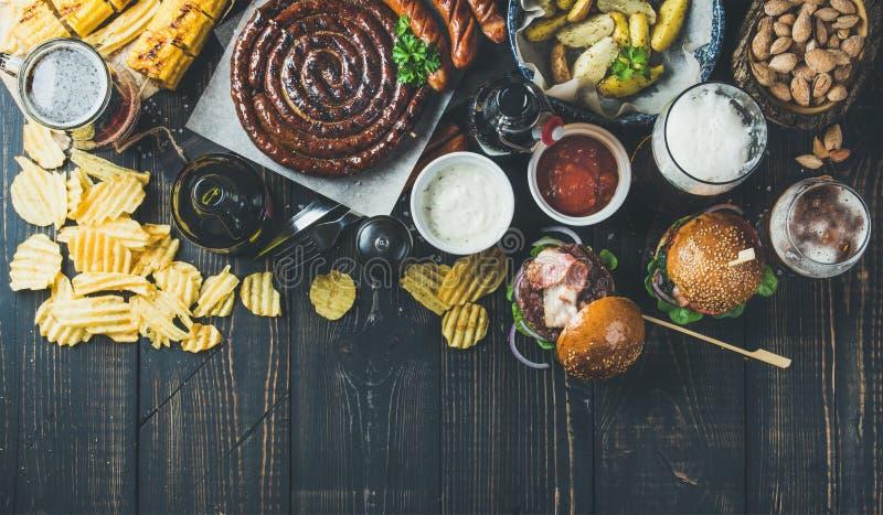 Variedad de cervezas, salchichas, hamburguesas, patata, maíz en fondo oscuro fotografía de archivo libre de regalías