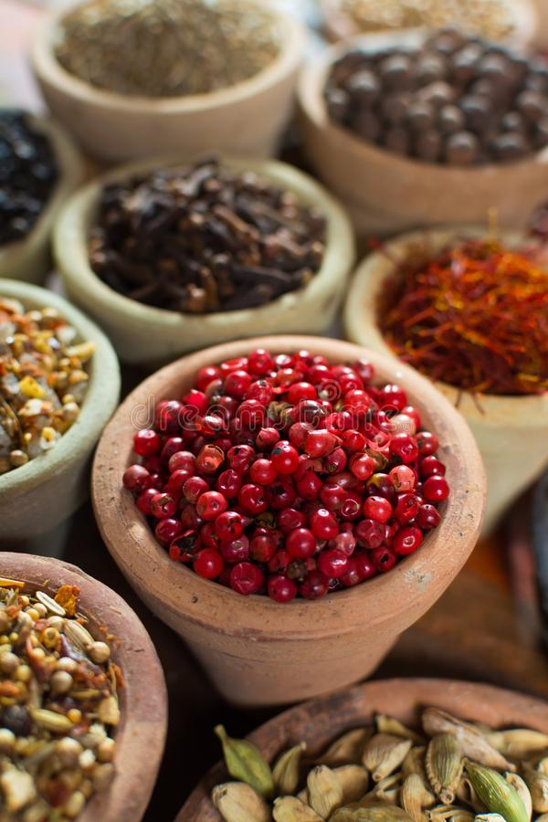 Variedad de diversas especias con el foco en la pimienta peruana rosada, imágenes de archivo libres de regalías