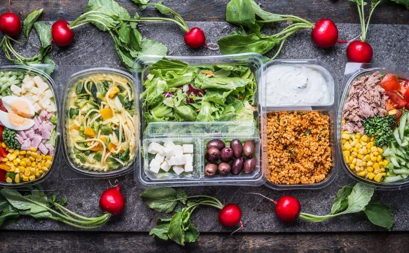Variedad de ensaladas de dieta limpias en paquete plástico y cinta métrica verde en el fondo rústico, visión superior Comida limp fotos de archivo libres de regalías