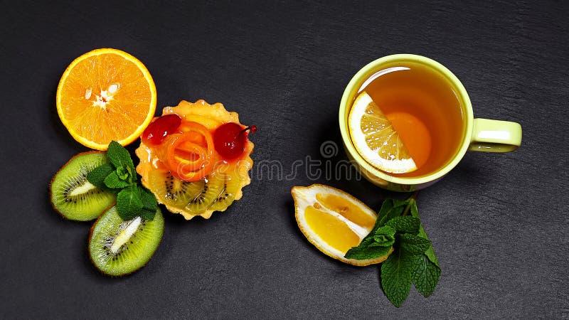 Variedad de frutas pomelo, naranjas, kiwi, limón, menta, torta, postre dulce agrupado, taza de la fruta de té junta en un tablero foto de archivo libre de regalías