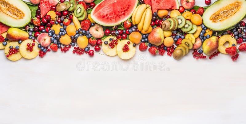 Variedad de frutas y de bayas orgánicas coloridas en el fondo blanco de la tabla, visión superior, frontera Alimento sano fotografía de archivo libre de regalías