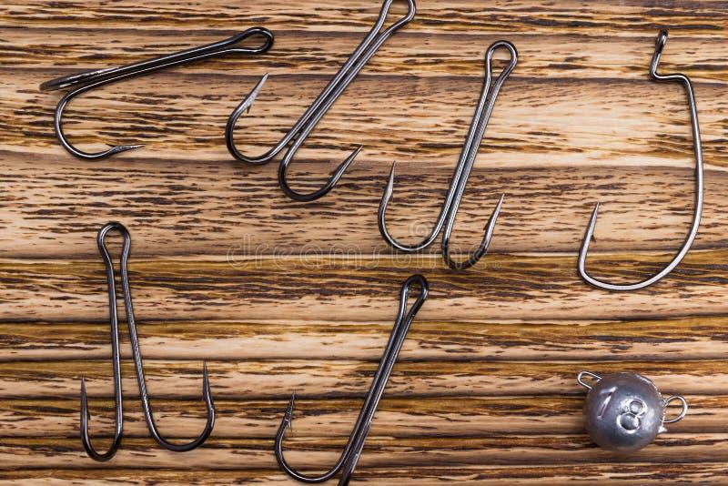Variedad de ganchos de pesca del hierro en un fondo quemado de madera foto de archivo libre de regalías