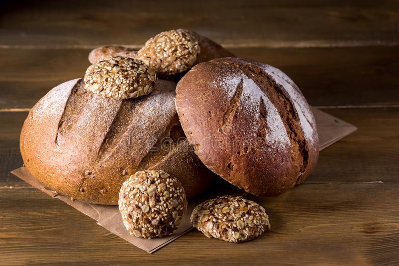 Variedad de panes Rye cocido fresco y de pan entero del grano en la variedad oscura de la foto del fondo de madera de la textura  foto de archivo libre de regalías