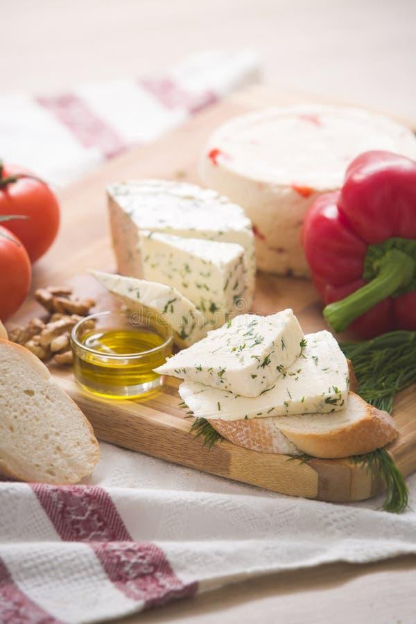 Variedad de queso y paprica e hierbas, aceite de oliva, aceitunas y pan hechos caseros en un tablero de madera imagen de archivo libre de regalías