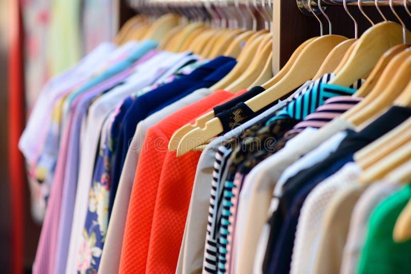 Variedad de ropa que cuelga en el estante fotografía de archivo