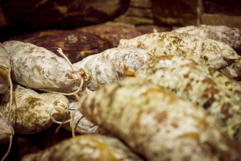 Variedad de salamis y de chorizos rojos españoles, cubierta con el cuero expuesto en el mercado imagen de archivo