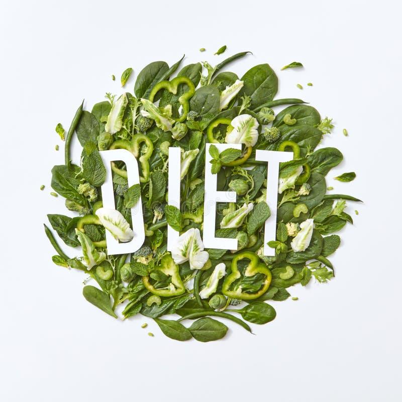 Variedad sana de verduras verdes col, espinaca, pedazos del espárrago del pepino y pimienta en un fondo gris con fotos de archivo