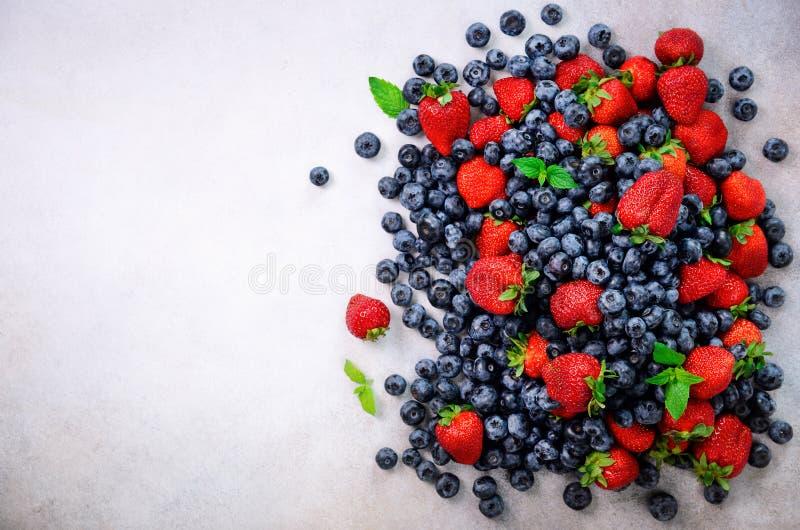 Variedade da morango, mirtilo, corinto, folhas de hortelã Quadro do alimento, projeto da beira Conceito do vegetariano e do veget fotografia de stock