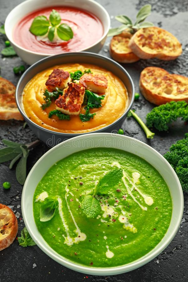 Variedade das bacias de sopa de creme: ervilha e hortelã doce, tomate e polpa da manjericão e de butternut com couve cozinhada e  imagem de stock